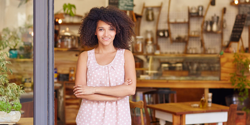 51356646 - beautiful young cafe owner proud of her small business standing smiling in the doorway of her coffee shop
